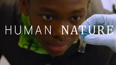 Photo of a young Black boy looking closely at a scientific specimen; the words