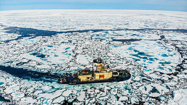Photograph of a yellow ice-breaking ship, Oden, cutting a path through an icy ocean on a sunny day