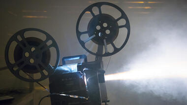 Photo of a film projector in a dark room, streaming light ahead of it
