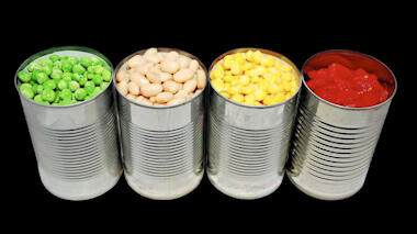 Photograph with a black background and a series of four tin cans with no labels, open at the top. From left to right, the cans hold green peas, tan-colored canellini beans, pale yellow chickpeas, and red diced tomatoes.