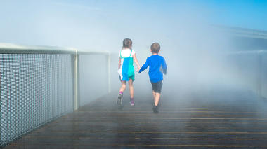 Kids walking on the Fog Bridge at the Exploratorium