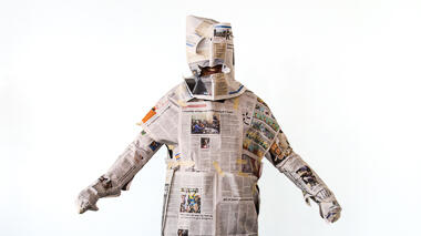 Person wrapped in newspaper