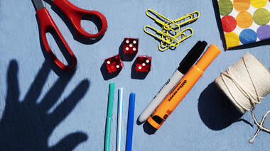scissors, paper clips, string and dice on a table